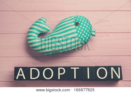 Black cubes with word ADOPTION and whale toy on color wooden background