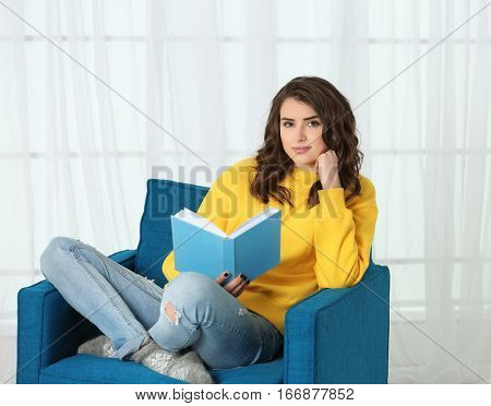 Beautiful young woman reading book while sitting in arm-chair at home