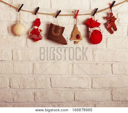 Several red brown and white Christmas decorations pinted on the rope on the brick white wall