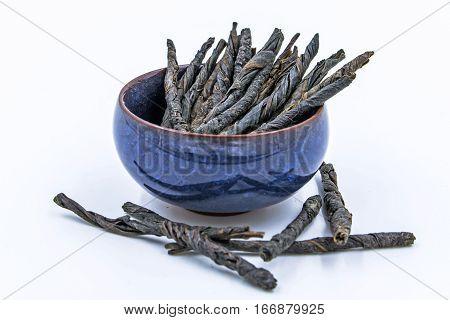 Kudin - Twisted Leaves of Ilex Latifolia Kudingcha. Bitter Chinese Green Tea in blue ceramic bowl isolated on white.