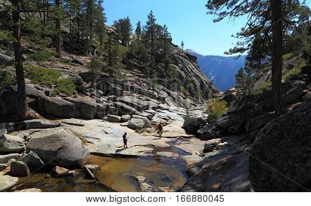 YOSEMITE NATIONAL PARK - SEP 21: Two hikers explore the dry, rocky creek bed of Yosemite Creek near the edge of Upper Yosemite Fall on Sep 21, 2015 at Yosemite National Park.