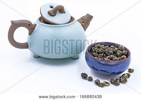 Chinese green tea Jasmine Pearl (Mo Li Long Zhu) in a blue ceramic bowl with small clay pot isolated on white.