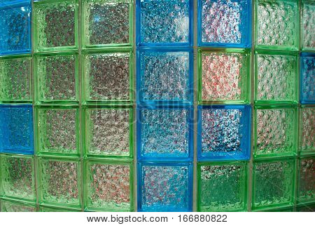 semicircular wall made of aquamarine and green glass tiles in the bathroom front closeup view