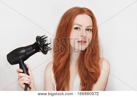 Young beautiful red-haired girl with a hairdryer in her hand on a white background.