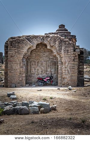 Parking the motorcycle in the ruins of Hampi. Heritage of UNESCO. Karnataka, India.