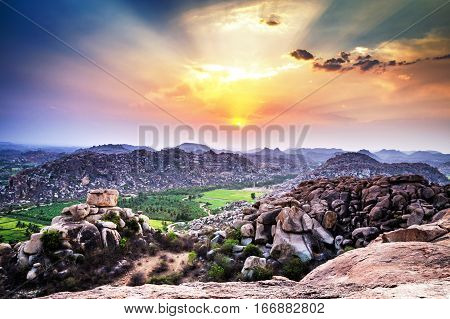 View to rice plantation from top of Hanuman monkey temple on hill at sunset in Hampi, Karnataka, India. Hampi sunset from hill.