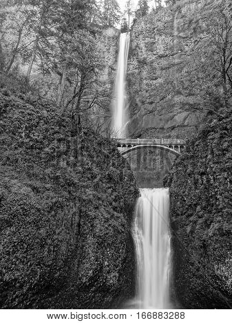 The two stages of Multnomah Falls which are the largest water falls in the state of Oregon with a footbridge crossing over the cliff side on a spring day.