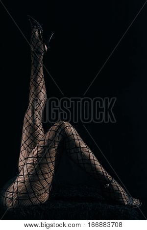 Low key photo of sexy slim beautiful legs in black net tights and high heel shoes lying on fur against black background