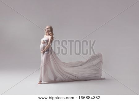 studio portrait of beautiful pregnant young woman in flying white dress with trail on light grey studio background