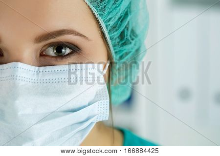 Close up portrait of female medical doctor or nurse wearing protective cap and mask. Surgery medical assistance hospital epidemic and healthcare concept.
