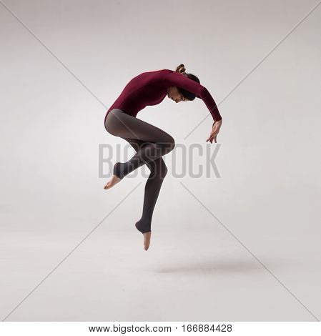 young beautiful woman dancer with long brown hair wearing maroon swimsuit jumping on a light grey studio background