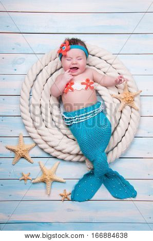 The newborn girl is crying in a mermaid suit is in the ropes on wooden boards