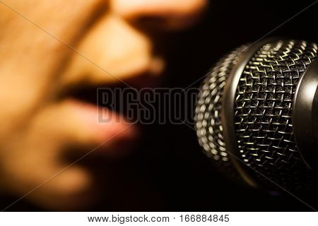 Close up image of a woman singing to a microphone.