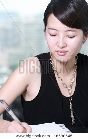 young asian business woman writing something