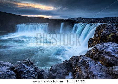 Godafoss Falls at Sunrise shows the water pouring over the edge and kicking up a misty cloud over the water.