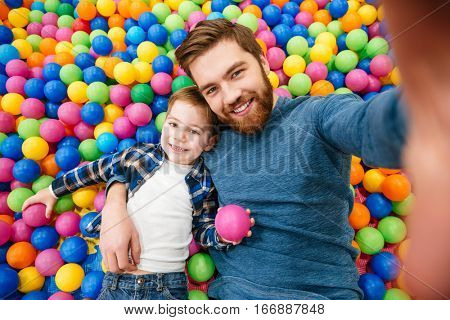 Happy little son with his dad having fun and taking selfie lying in pool with colorful balls