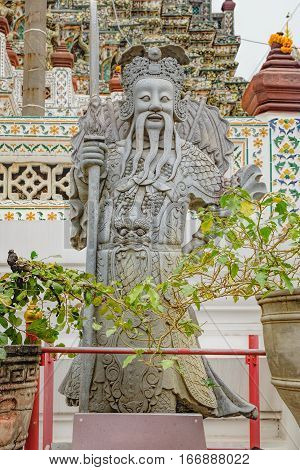 Sculpture of Chinese-style guardian in Temple of Dawn, Wat Arun, Bangkok, Thailand. Showing glass and ceramics elements combination in Thai style on the pagoda base.