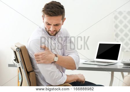 Handsome young man suffering from shoulder pain in office