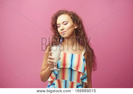 Young beautiful woman with milk shake on color background