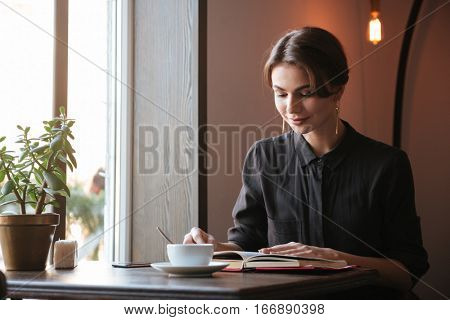 Photo of gorgeous young lady sitting at the table reading book in cafe and looking aside while drinking coffee.