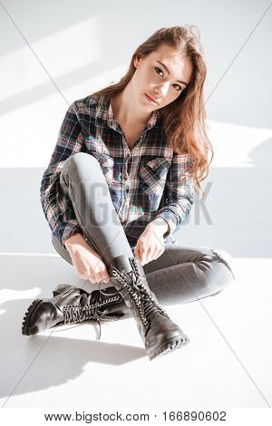 Picture of young woman sitting on floor at studio over white background and posing