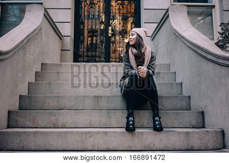 Full length portrait of a smiling woman in hat sitting on the house stairs outdoors and looking away