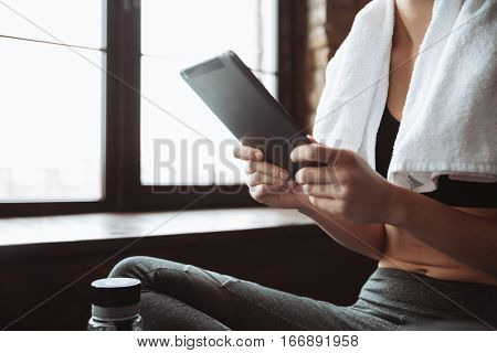 Cropped picture of young fitness woman with towel sitting in gym while using tablet computer.