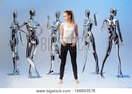 attractive woman in jeans on background of many  metallic shiny mannequins. uniqueness.