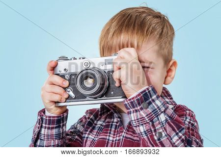 Close up portrait of a little boy taking picture with retro camera over blue background
