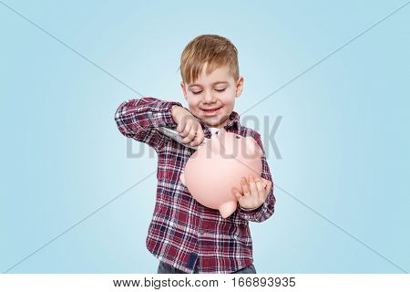Portrait of a smiling little boy putting paper money inside money box over blue background