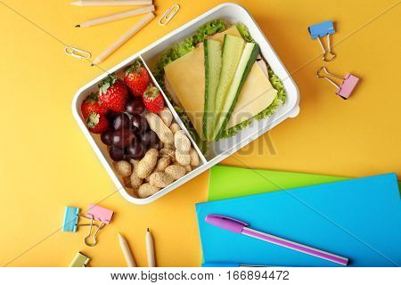 Tasty sandwich and fruits in lunchbox and stationery on yellow background