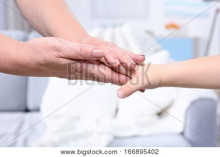 Hands of grandmother and her grandchild