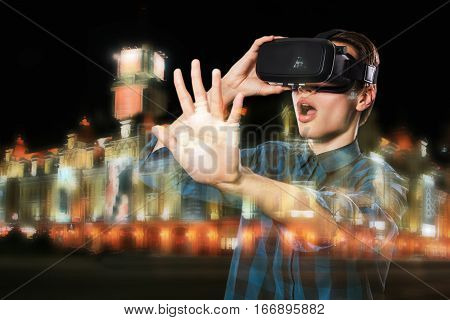Double Exposure Of Young Man Using Vr Headset Glasses For Virtual Reality  Goggles, Night City.