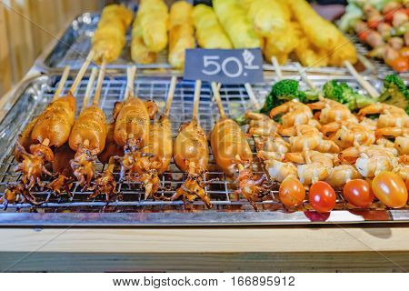 Squid and shrimp on skewers are being grilled by a street vendor in Thai street night market. Deep fried snacks with price tag fresh and hot Thai food.