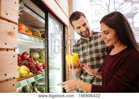 Cheerful young couple choosing and buying vegetables in grocery shop
