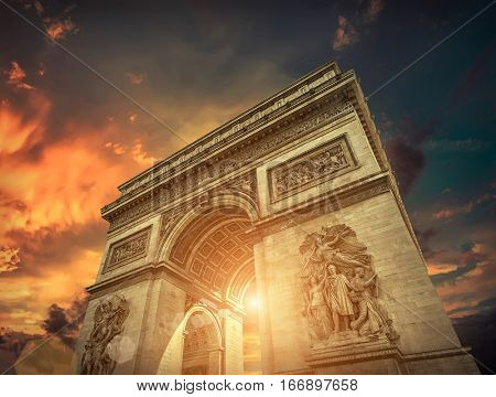 Arc de Triomphe in Paris under sunset sky with clouds. One of symbols of France and one of the most popular tourist places in the world.