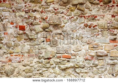 old wall made of different stones and cement