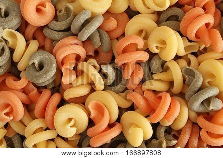 Food background - uncooked three-colored Trottole durum wheat pasta with basil and tomato