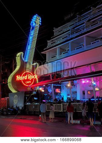Neon guitar with Hard Rock Cafe. Fhuket, Thailand - May 28, 2016 Impressive neon guitar in front of a music club Hard Rock Cafe in Fhuket in Thailand.