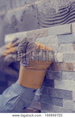 Close-up of hands of tiler worker in gloves pressing brick tiles to stick it to the wall.