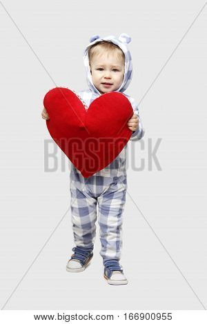 Children, people, Happy Valentine`s day concept - Adorable baby boy in sleepwear  holding a big red heart.