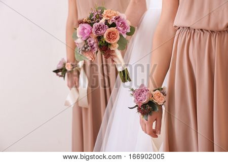 Bride holding wedding bouquet and bridesmaids with beautiful boutonniere, closeup
