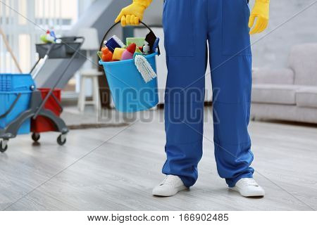 Young man holding bucket with cleaning equipment and supplies indoors