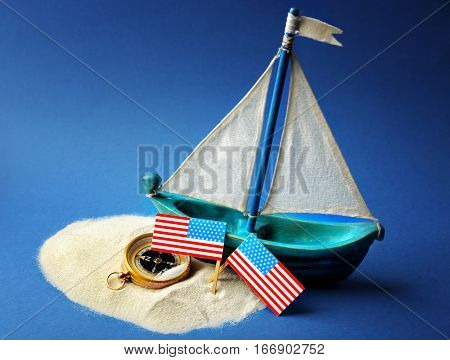 Wooden boat, USA flags and compass on blue background. Columbus Day concept
