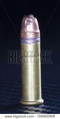 Mangled bullet on top of a rimfire cartridge on graphite