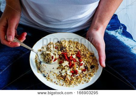 Eating diet breakfast bowl. Homemade granola milk seeds honey and dry fruits in white ceramic bowl in woman' s hands selective focus. Clean eating dieting detox vegetarian food concept