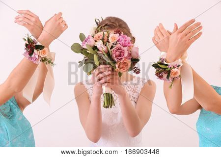 Bride holding wedding bouquet and bridesmaids with beautiful boutonniere on white background