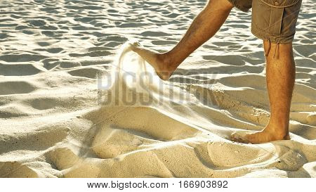Legs of tanned man in khaki shorts sieving sand with feet. Barefoot human playing in desert. Senseless act and loneliness concept. Close-up. Side view.