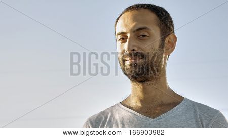 Tanned man with beard and in gray t-shirt smiles with teeth. Cheerful person. Human under sunlight. Joy, happiness and consent concept. Close-up. Front view.