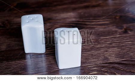 Pair of white minimalistic salt and black pepper pots. Traditional set of condiments on wooden restaurant dining table. Close-up.